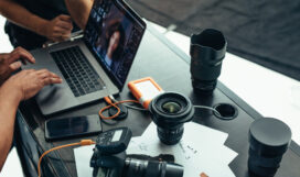 Photographer looking at photos after a photo shoot on a laptop. Photographer editing photos on laptop with camera and lens placed on table.